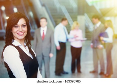 Young smiling pretty bussinesswoman over team background