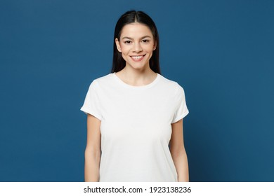 Young smiling pretty happy cute cheerful positive nice attractive latin woman 20s wearing white casual basic blank print design t-shirt looking camera isolated on dark blue background studio portrait
