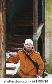 Young smiling red-bearded man stands near the old abandoned houses while traveling in the winter.