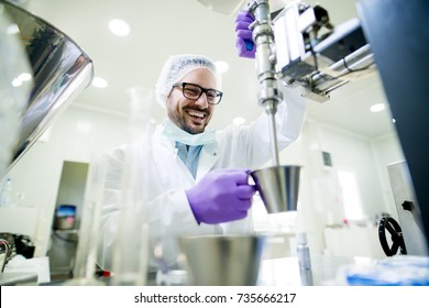Young smiling researcher with gloves and hair protection working on the lab machine.