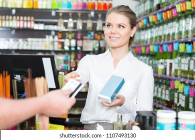 Young smiling saleswoman taking credit card while serving client in perfume shop