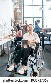 Young smiling seamstress with tablet sitting in wheelchair against group of colleagues in workshop