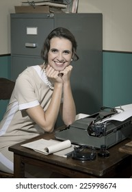 Young smiling secretary at office typing on a vintage typewriter and looking at camera.