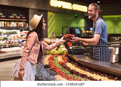 Young smiling seller in apron behind counter happily giving strawberries to customer in modern supermarket