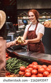 Young smiling seller in apron behind counter with vegetables happily giving bananas to customer in modern supermarket