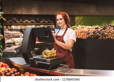 Young smiling seller in apron behind counter with vegetables weighing bananas on scale in modern supermarket