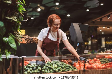 Young smiling seller in apron standing behind counter with vegetables happily working in modern supermarket