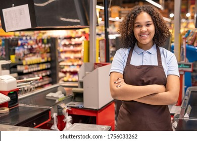 Young smiling shop assistant or cashier in workwear crossing arms by chest while standing by workplace in supermarket environment