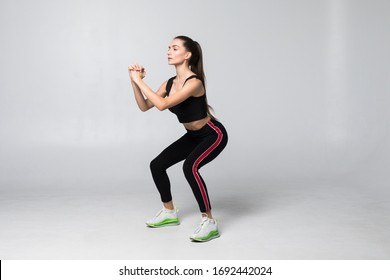 Young smiling sport woman doing squats with dumbbells on gray background