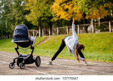 Young smiling sporty woman with baby stroller in warm clothes warming up - doing stretching exercises in track of stadium. Autumn, fall and motherhood concept.