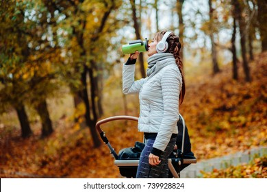 Young smiling sporty woman with headphones and baby stroller in warm clothes drinking hot tea from thermos cup after workout outdoor in park. Multitasking, sport and happy motherhood concept.