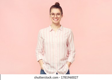 Young smiling student girl dressed in shirt and jeans, wearing round glasses and hair tied in bun, holding hands in pockets, isolated on pink background