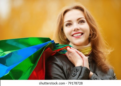 Young smiling student with purchases in packages comes back from shop against yellow autumn nature.