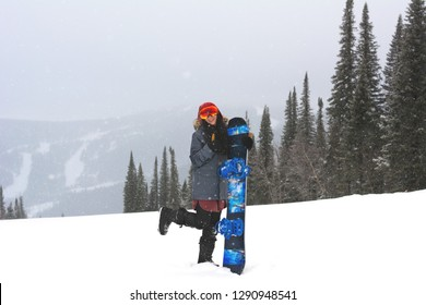 a7f370ccbd8 Young smiling stylish snowboarder girl stand bending one leg on top of a  mountain and holding