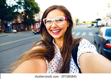 Young smiling teen happy woman making selfie on the street, ling hairs, bright make up and cute clear glasses, traveling alone, having fun, positive mood, joy, vacation.