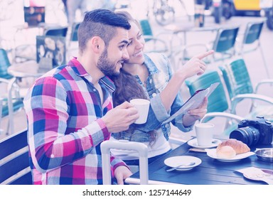 Young smiling tourist couple with photocamera and map at open-air cafe. Focus on man