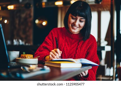 Young smiling trendy hipster girl writing organisation plan in notebook enjoying lunch time at college cafeteria, cheerful caucasian woman studying at academy campus using textbook for education