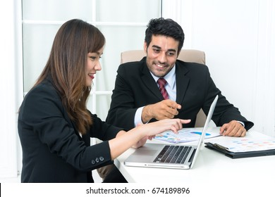 Young Smiling two businesspeople using notebook computer during the meeting in modern office. Businessman and businesswoman discussing and pointing to modern laptop in conference room.