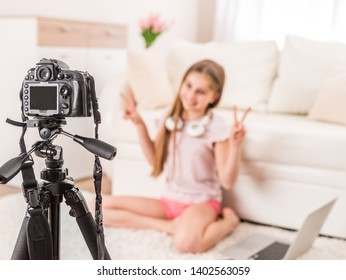 Young smiling videobloger teen girl is pointing at camera in living room