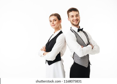 Young smiling waiter and beautiful waitress in white shirts and vests sstanding back to back happily looking in camera with arms folded over white background