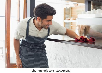 Young smiling waiter cleaning countertop with sponge