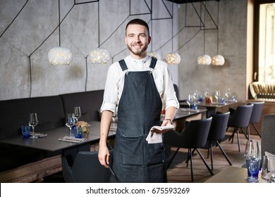 A young, smiling waiter in a restaurant, standing next to the tables with a glass of wine. Dressed in an apron, will take an order holding a notebook and a pen