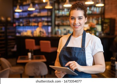 Young smiling waitress in apron and t-shirt standing in front of camera while using touchpad and meeting guests in cafe