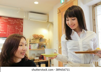 Young smiling waitress  serving coffee at a cafe,