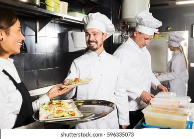 Young smiling waitress taking order of meal from restaurant  kitchen