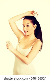 Young smiling woman applying anti perspirant.