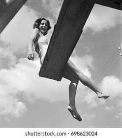 Young smiling woman in bathing suit sitting on diving board