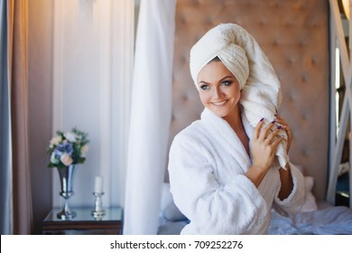 Young smiling woman in a Bathrobe, interior of hotel