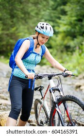 Young smiling woman with bicycle wade the mountain creek on summer day