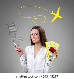 Young smiling woman buying boarding pass with smart phone online on grey background with shopping baskets and graphic airplane flying