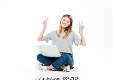 Young smiling woman in casual clothes using laptop computer and showing peace gesture isolated over white