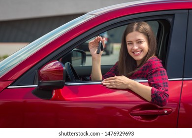 Young smiling woman in casual dress driving modern car