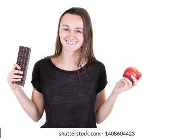 Young smiling woman with chocolat and an apple having doubts