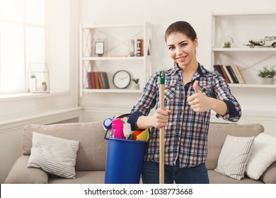 Young smiling woman with cleaning equipment ready to clean house, showing thumb up gesture. Professional cleaning service concept, copy space