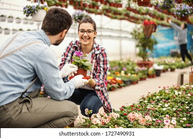 Young smiling woman crouching with her colleague and talking about flowers.
