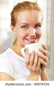 young smiling woman with a cup at home