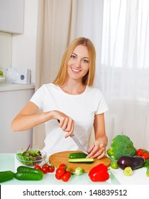 Young smiling woman cutting vegetables at the kitchen
