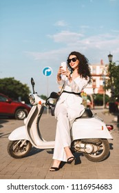 Young smiling woman with dark curly hair in white costume and sunglasses sitting on white moped and happily taking photos on cellphone on street with city view on background