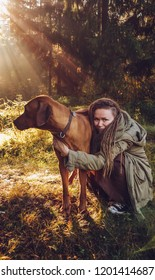 Young smiling woman with dreadlocks in autumn fall forest in the morning sunshine playing with a dog ridgeback