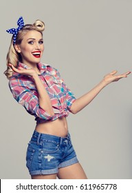 Young smiling woman dressed in pin-up style, showing something or copyspace area for text or slogan. Caucasian blond model posing in retro fashion and vintage concept studio shoot, on grey background.