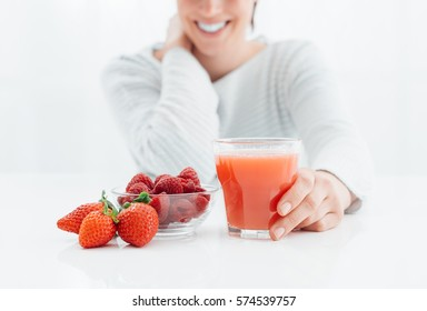Young smiling woman drinking an healthy natural red juice made with berries, healthy diet and vitamins concept