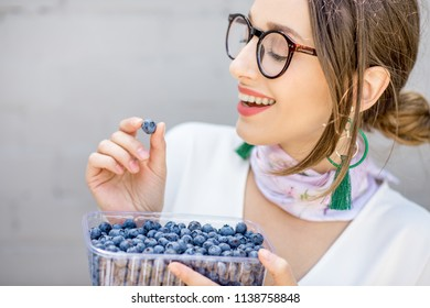 Young smiling woman eating bluberries outdoors on the gray wall background