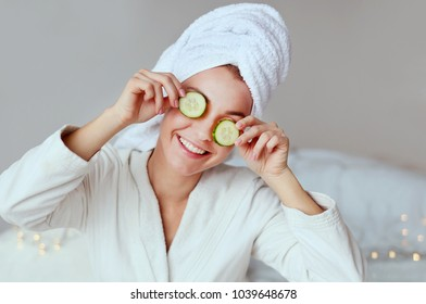 Young smiling woman enjoying her Spa morning and wake up. Happy girl in a towel with mask on face and cucumber in the bedroom .Beauty skin care