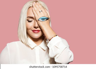 Young smiling woman with eye painted on her hand. Studio portrait of fashionable model on pink background. Beautiful model with blonde hair. Concept of flirting and fun.