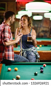 Young smiling woman flirting with man during billiard game