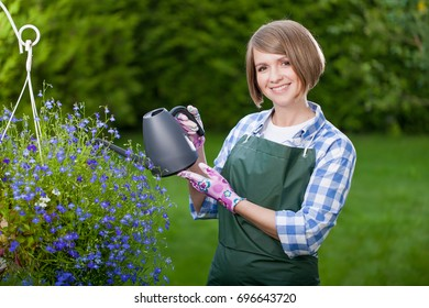Young smiling woman florist working in the garden.